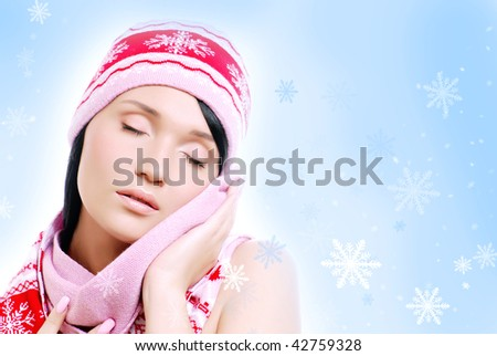 Portrait of the Sensuality fashion woman in  red winter hat and scarf . Falling snowflake in background