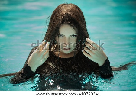 Portrait of the sexy woman relaxing in black fashion dress in pool. Creative photosessin of beautiful caucasian girl.  - stock photo