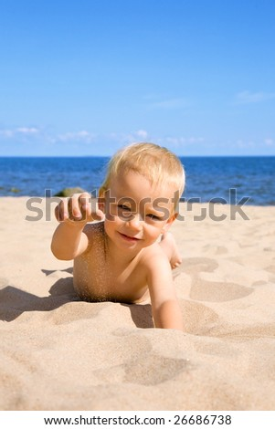 portrait of the small boy on a sunny beach - stock photo