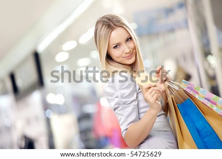 Portrait of the smiling blonde in shop with a credit card in a hand - stock photo