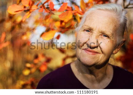 Portrait of the smiling elderly woman. A photo on the autumn background - stock photo