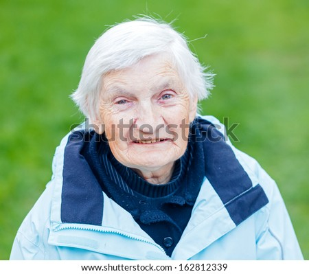 Portrait of the smiling elderly woman on outdoors - stock photo