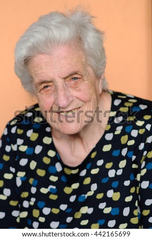 Portrait of the smiling elderly woman, sitting outdoor - stock photo