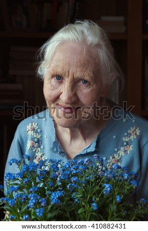 Portrait of the smiling elderly woman with flowers, mother day - stock photo