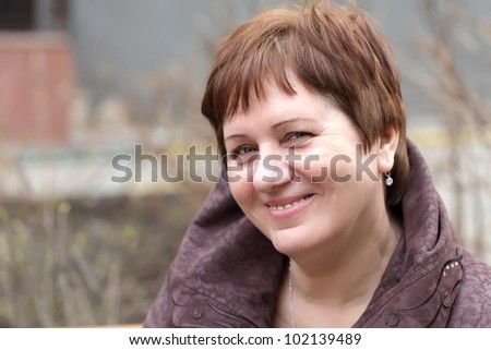 Portrait of the smiling mature woman outdoor - stock photo