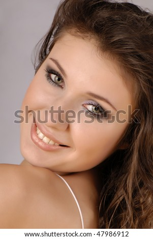 Portrait of the smiling young beautiful woman with a slightly opened mouth