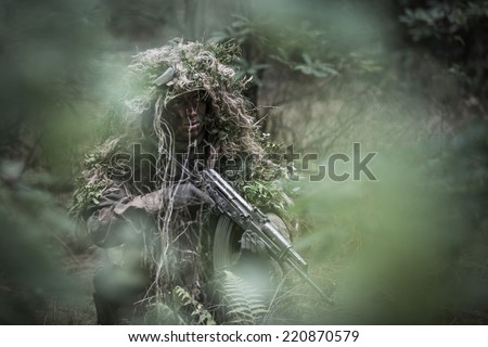 portrait of the soldier wearing ghille suit, hidden in forest - stock photo