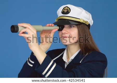 Portrait of the woman - captain with spyglass on a blue background