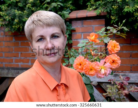 Portrait of the woman of average years with roses against a brick protection - stock photo