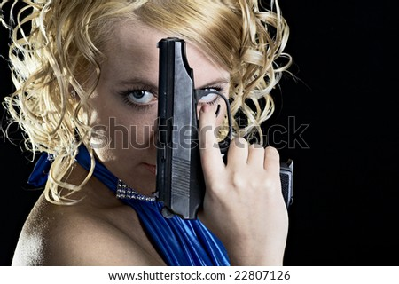 portrait of the woman with gun isolated on black background - stock photo