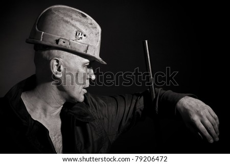 Portrait of the worker on a black background - stock photo