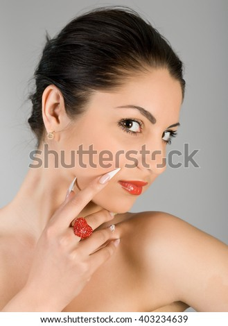 Portrait of the young beautiful brunette on a gray background - stock photo