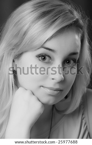 Portrait of the young beautiful girl on a dark background. Black and white
