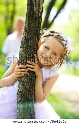 Portrait of the young beautiful happy girl near the tree - stock photo