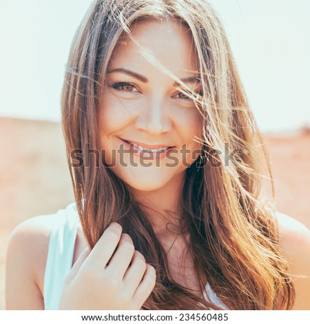 Portrait of the young beautiful smiling woman outdoors enjoying summer sun. wind in hair. Photo with instagram style filters - stock photo