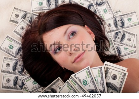 Portrait of the young beautiful woman lying on background from banknotes