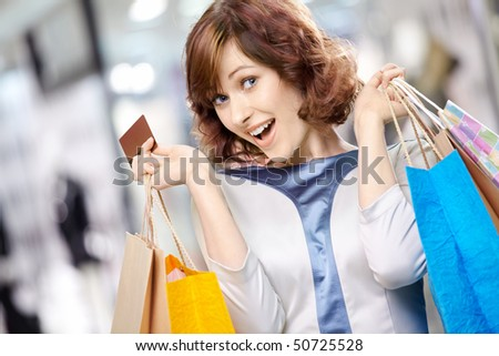 Portrait of the young beautiful woman smiling in shop with bags and a credit card