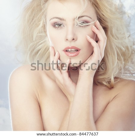 Portrait of the young blond lady on a sky background - stock photo