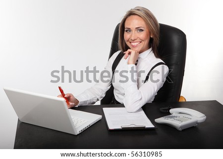 Portrait of the young business woman sitting at a desktop - stock photo