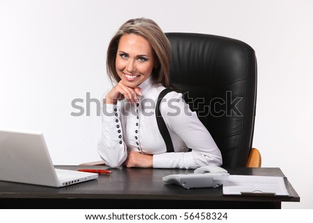 Portrait of the young business woman sitting at a desktop