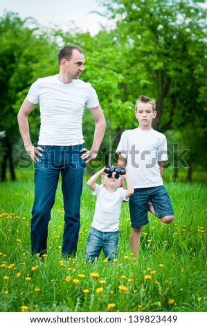 Portrait of the young father with sons in park - stock photo