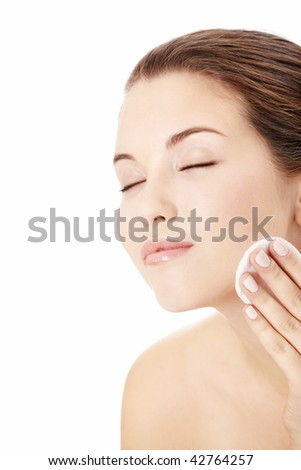 Portrait of the young girl applying on a face a cosmetic pad, isolated - stock photo