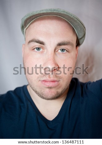 Portrait of the young man in a cap, a studio photo