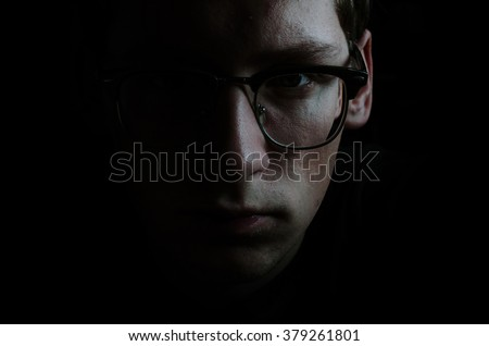 Portrait of the young man in glasses in low key - stock photo