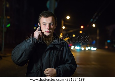 Portrait of the young man in the street night city with phone - stock photo