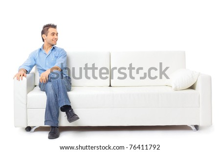 Portrait of the young man in white on sofa - stock photo