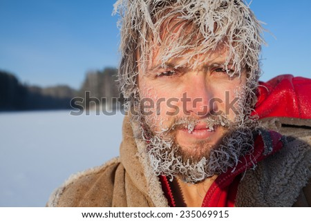 Portrait of the young man with frozen icy hairs on head and beard - stock photo