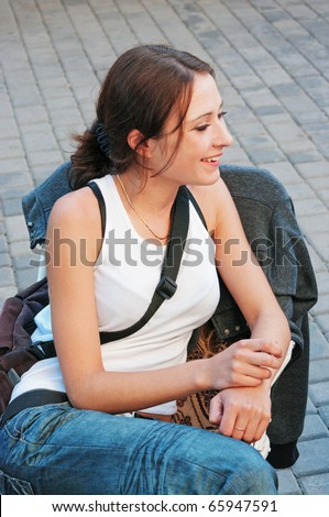 Portrait of the young smiling girl sitting on a chair in city street