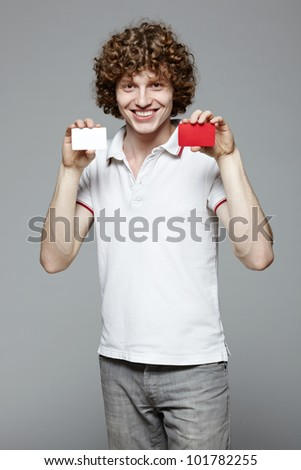 Portrait of the young smiling man holding two blank credit cards, isolated on gray background - stock photo