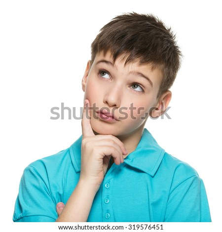 Portrait of the young smiling  thinking teen boy  looks up in casuals - isolated on white. - stock photo