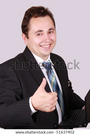 Portrait of the young successful businessman,isolated on gray background. The Smiling man has raised upwards thumb. The Concept of this picture: business, success, work