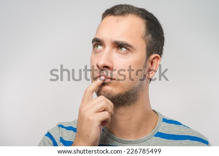 Portrait of the young  thinking man looks up   - stock photo