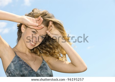 Portrait of the young woman against the blue sky and clouds - stock photo