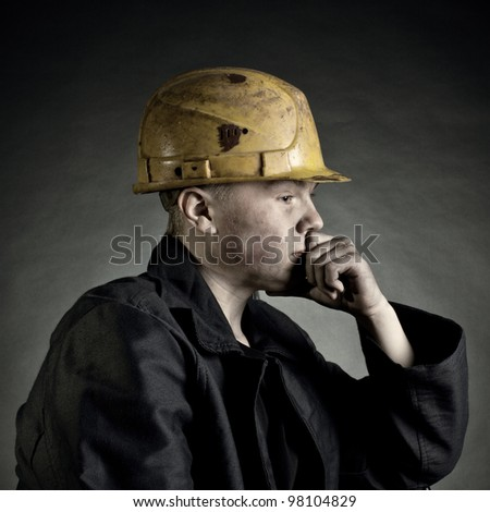 Portrait of the young worker against a dark backgroun - stock photo