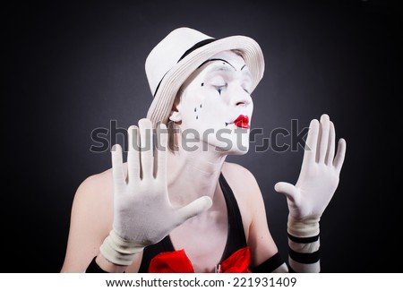 Portrait of theatrical mime on a black background - stock photo