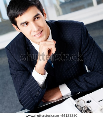 Portrait of thinkihg businessman with documents at office - stock photo
