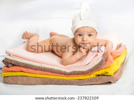 Portrait of thinking baby boy. baby on colorful towels stack