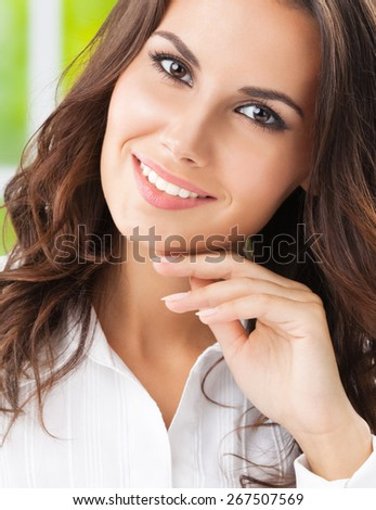 Portrait of thinking cheerful businesswoman at office - stock photo