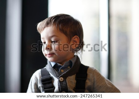 Portrait of thinking child on the window background - stock photo