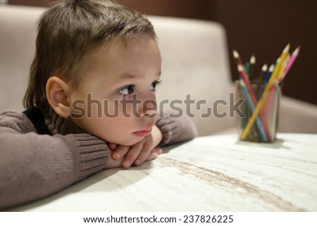 Portrait of thinking kid in a cafe - stock photo