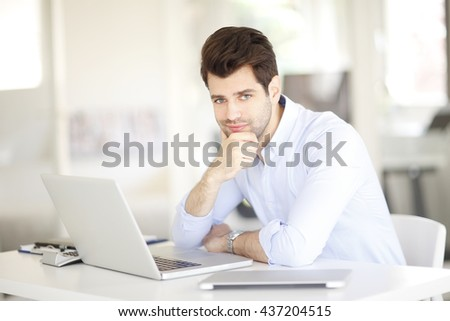 Portrait of thinking sales assistant man working on laptops while sitting at his workstation.