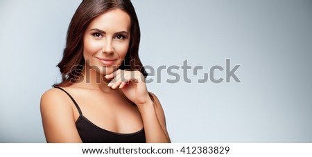 portrait of thinking young woman in black tank top clothing, on bright grey background, with blank copyspace area for slogan or text - stock photo