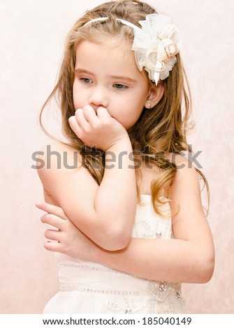 Portrait of thoughtful adorable little girl in princess dress isolated - stock photo
