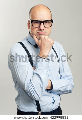 Portrait of thoughtful bald man in glasses isolated over gray background - stock photo
