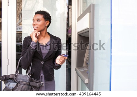 Portrait of thoughtful beautiful african american business woman holding credit card at bank cash point in city, outdoors. Professional ethnic woman accessing funds in slick bank. Stylish lifestyle.