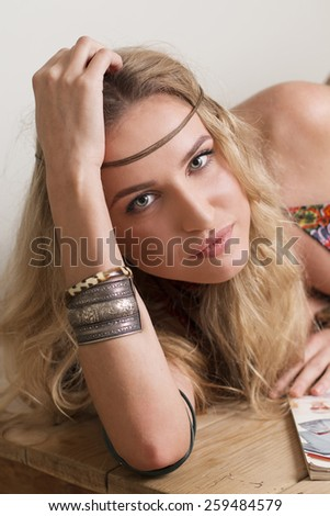 portrait of thoughtful blond hippie womanlying on wooden table - stock photo